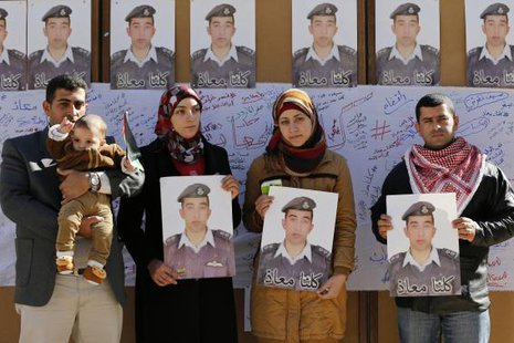 Relatives of Islamic State captive Jordanian pilot Muath al-Kasaesbeh hold pictures of him as they join students during a rally calling for his release, at Jordan University in Amman February 3, 2015. CREDIT: REUTERS/MUHAMMAD HAMED