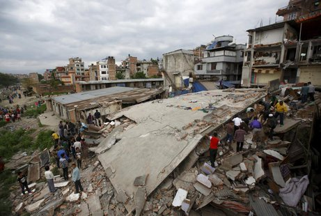 People gather near a collapsed house after a major earthquake in Kathmandu, Nepal April 25, 2015. REUTERS/Navesh Chitrakar