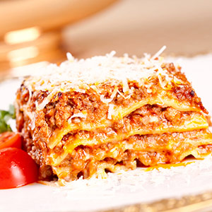 Plate of lasagna with tomato garnish.