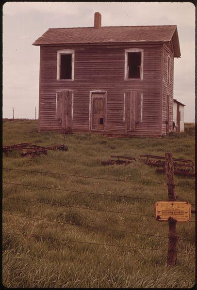 An abandoned farmhouse behind a fence with a sign posted by a Camp Grove sportsmen's club and the Illinois Department of Conservation.