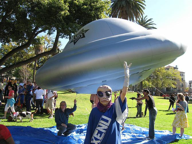 Individual in a Xenu costume, standing next to inflatable float by group of Raelians
